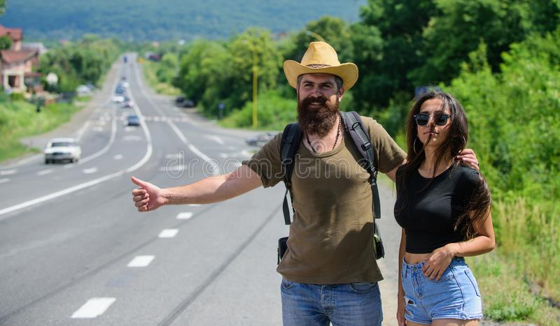 Travellers try to stop car. Hitchhiking is one of cheapest ways of traveling. Couple hitchhikers travelling summer sunny royalty free stock images
