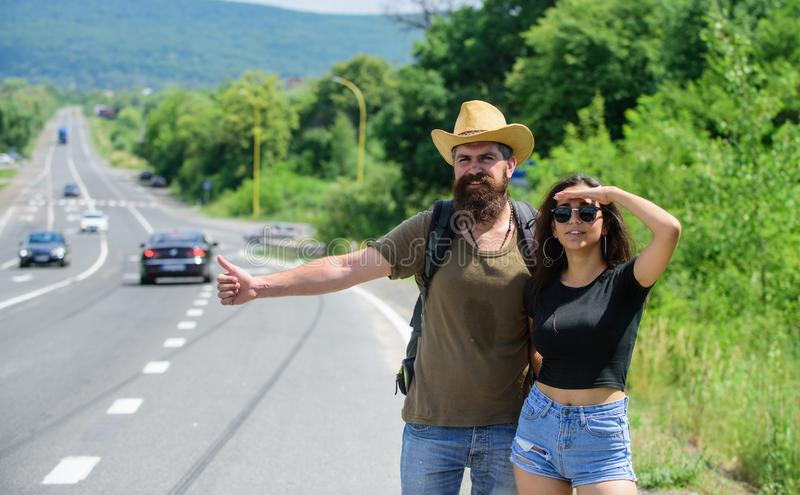 Travellers try to stop car. Hitchhiking is one of cheapest ways of traveling. Couple hitchhikers travelling summer sunny. Day. Couple travelers men and girl stock image