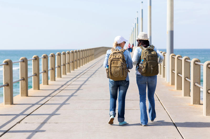Travellers walking pier. Travellers walking on a beach pier during thier holiday vacation stock image
