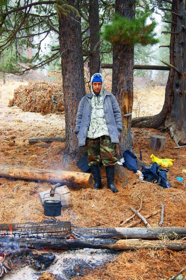 Travellier ao lado das fogueiras na madeira imagens de stock royalty free