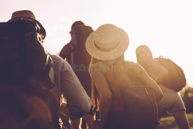 Travelling with best friends. Rear view of young people with backpacks walking together stock image