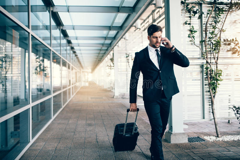 Travelling businessman making phone call stock photography