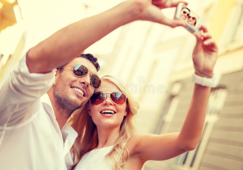 Travelling couple taking photo picture with camera. Summer holidays, travel, vacation, tourism and dating concept - travelling couple taking photo picture with royalty free stock photography
