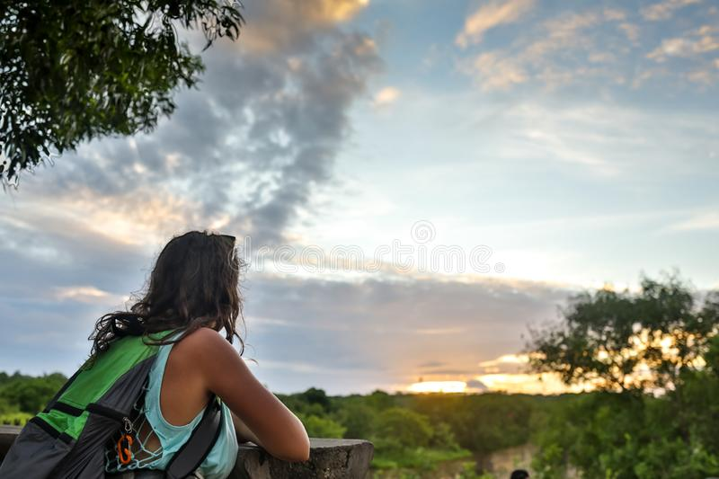 Travelling girl enjoying view to beautiful rural scenery after sunset. Happy woman looking at horizon in countryside. royalty free stock photo