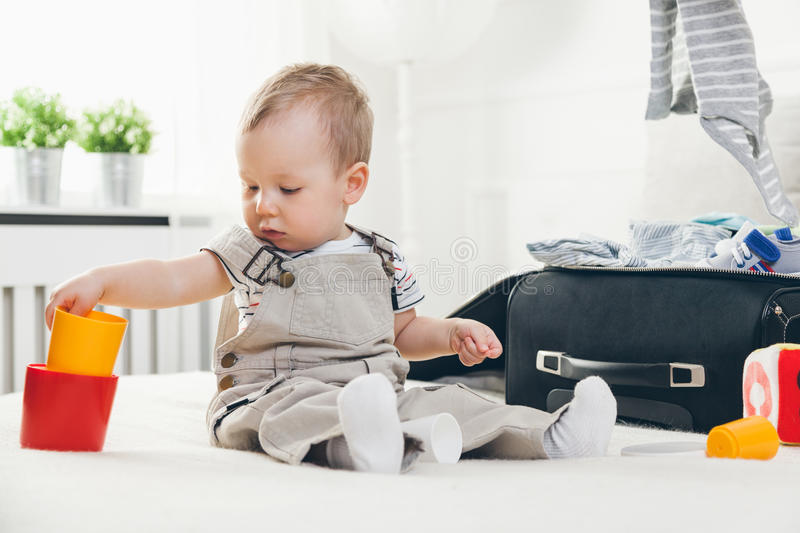 Travelling with kids. Cute toddler packing clothes and toys for holiday royalty free stock photography