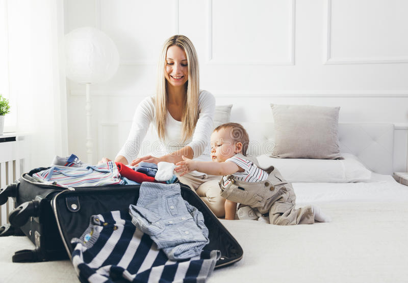Travelling with kids. Happy mother with her child packing clothes for holiday stock photography