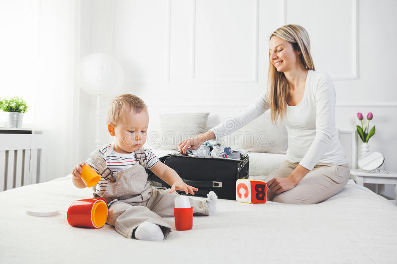 Travelling with kids. Happy mother with her child packing clothes for holiday stock images