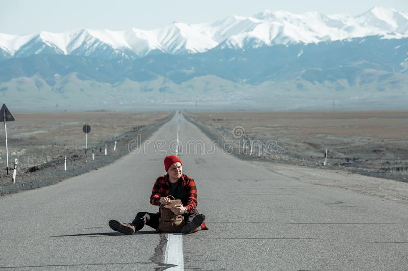 Travelling man sitting in middle of the road with backpack. Travelling young man in red shirt and hat sitting in the middle of straight road with backpak in stock image