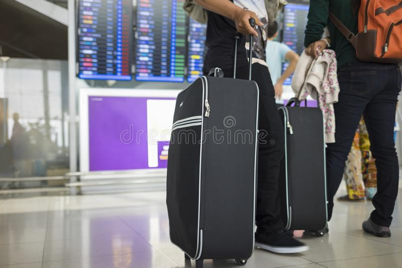 Travelling suitcase against flight information board on background. Concept of travel by airplane stock photo
