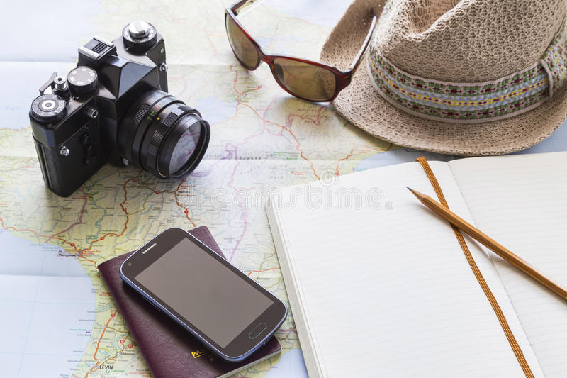 Travelling. Table with open map showing plans for travelling and related items including camera passport smartphone sunglasses hat and journal royalty free stock photography