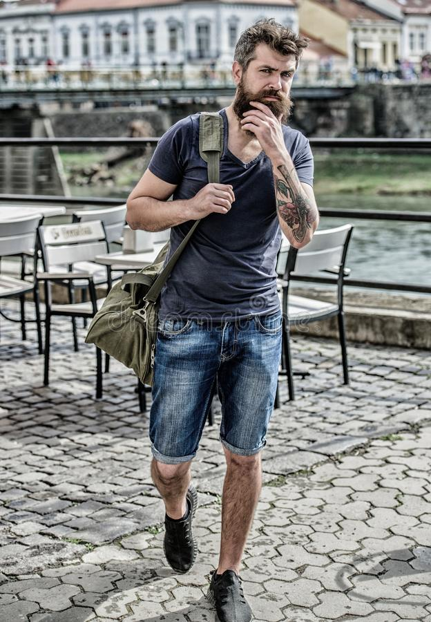 Travelling and vacations concept. Tourist explore city with luggage. Heavy bag on his shoulder. Carry things in big bag. On shoulder. Muscular man with beard stock photography