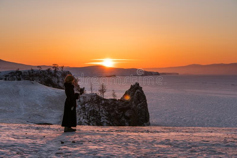 Travelling in winter at lake Baikal in Irkutsk, Russia. Winter landscape in sunset with young woman using mobile smart phone and e stock images