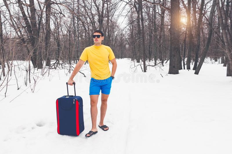 Travelling from winter to summer. Young man stands in summer clothers on the snow and dreams of vacation, sea, warm exotic country stock image