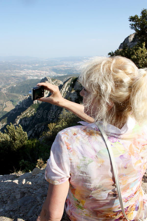 Travelling woman sitting on the rocks and photographs stock image