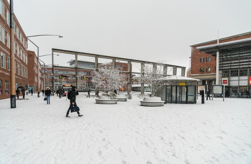 Travelors die en de stations ingaan verlaten, tijdens een sneeuwdag stock afbeelding