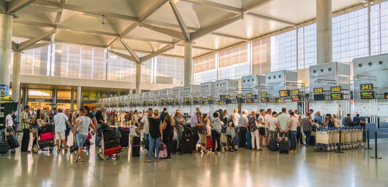 Travelors que verifica dentro nos contadores do aeroporto de Malaga fotografia de stock royalty free