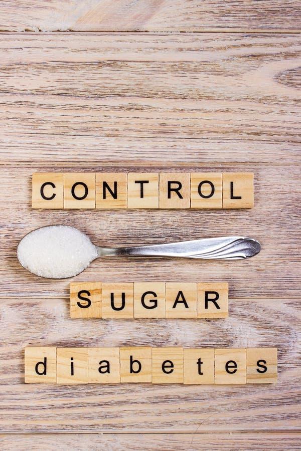 Traver träbokstäver och socker för sockersjukakontrollkvarter på en sked royaltyfri fotografi