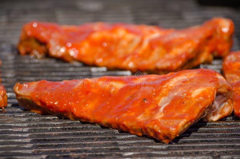Travers de porc sur le gril avec la marinade chaude photographie stock libre de droits