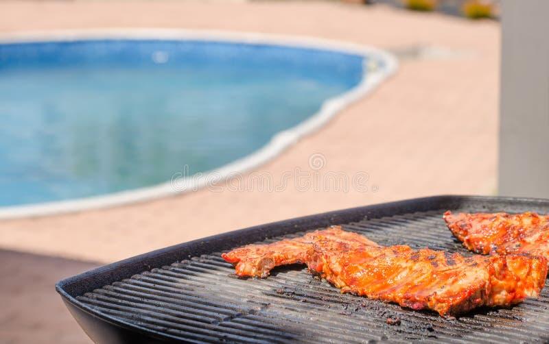 Travers de porc sur le gril avec la marinade chaude images stock