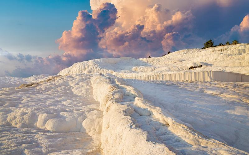 Travertine terrace formations left by flowing thermal springs in Pamukkale, literally. Sunset view of amazing Pamukkale. Travertine terrace formations left by stock image