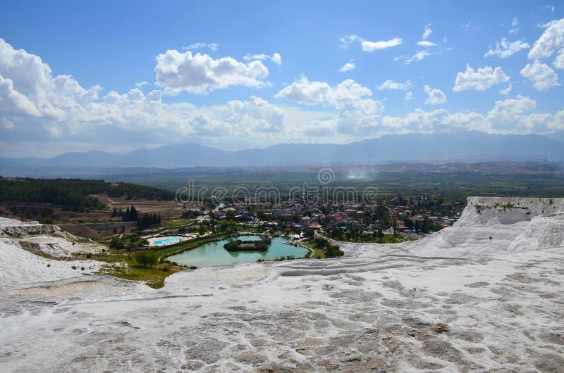 Travertins blancs comme neige dans la perspective des montagnes, de la ville et du ciel bleu d'été avec des nuages dans Pamukkale images stock