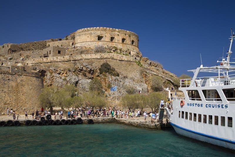 Travesía a la isla de Spinalonga Bote pequeño en la laguna azul Fortaleza de Spinalonga en la isla de Creta, Grecia fotografía de archivo libre de regalías