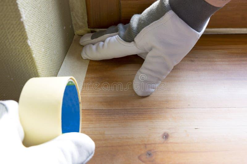 Travesaños de protección de la ventana del trabajador del pintor con la cinta adhesiva antes de pintar en casa el trabajo de la m foto de archivo