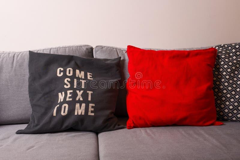 Travesseiros vermelhos e cinzentos num sofá cinza - com o texto Sente-se ao meu lado fotografia de stock