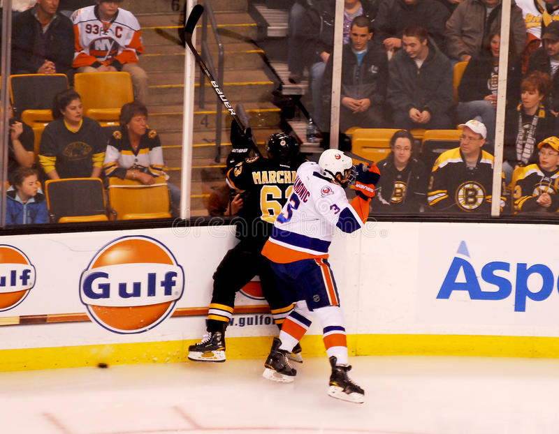 Travis Hamonic New York Islanders. New York Islanders defenseman Travis Hamonic pins Boston Bruins forward Brad Marchand against the boards stock photo