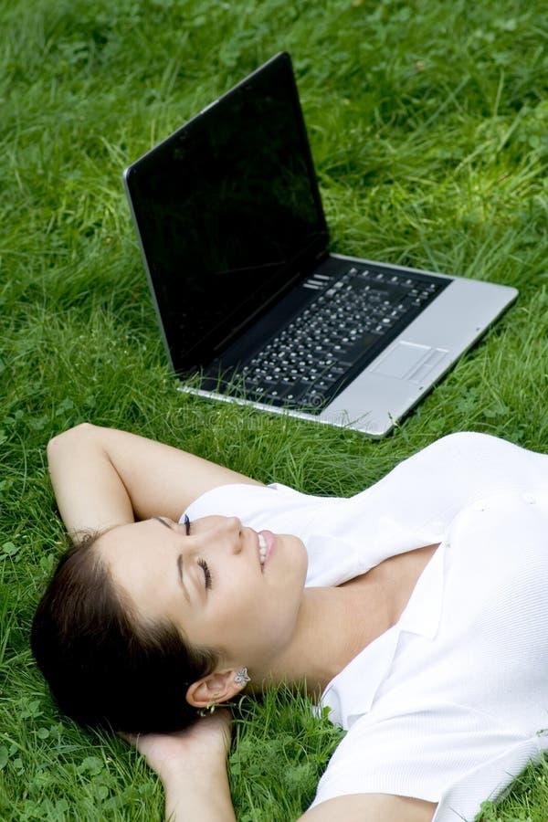 trawa laptopa leżącego kobieta zdjęcia stock