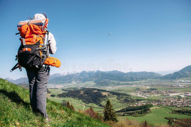 Traweler de la mujer con estancia de la mochila en el top de la colina Imagen activa del concepto de la gente imágenes de archivo libres de regalías