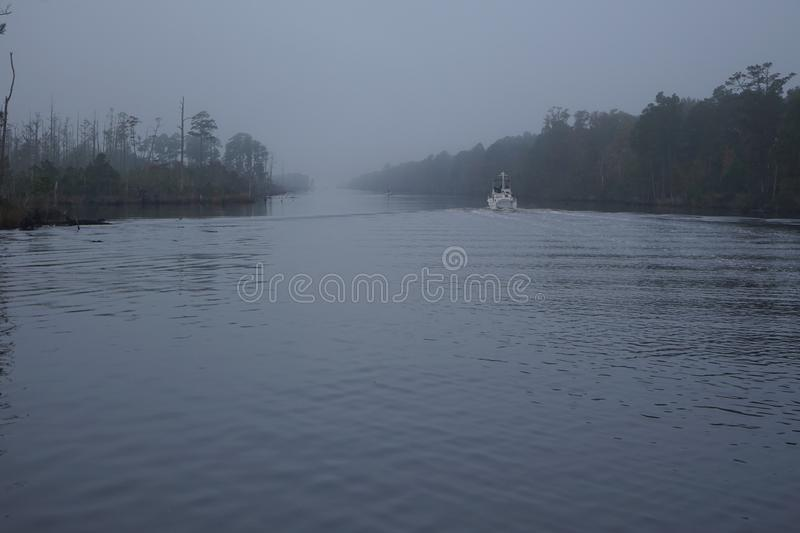 Trawler Boat travels the waterway in fog. A trawler boats down the intracoastal waterway in fog and low visibility stock image