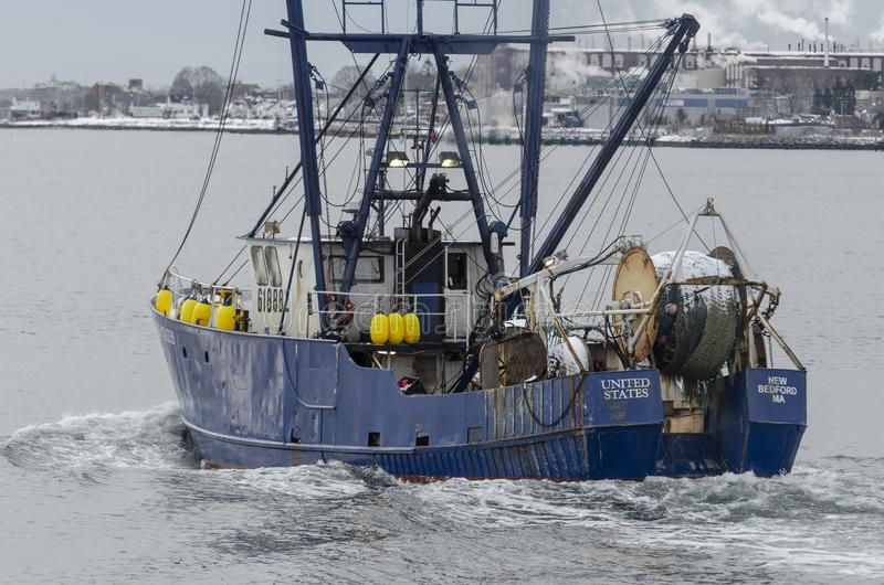 Trawler United States leaving port. New Bedford, Massachusetts, USA - December 4, 2019: Commercial fishing boat United States passing factory on her way out of stock photos