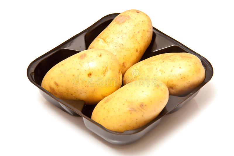 Tray of baking potatoes stock photography