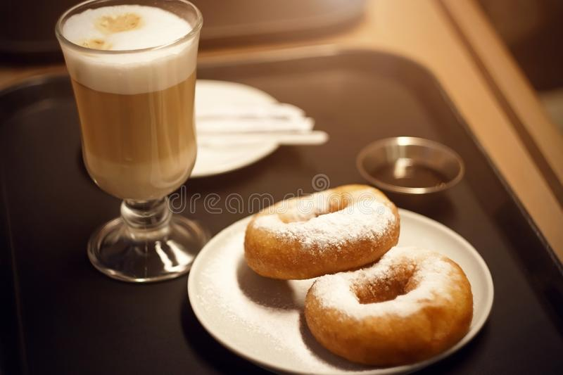 On the tray is a Breakfast with a coffee drink and two donuts. On the tray is a delicious Breakfast with an invigorating coffee drink and two donuts sprinkled stock photography