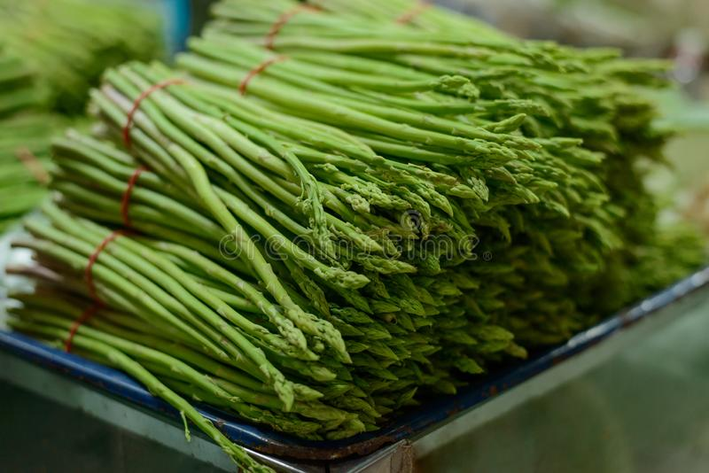 Tray with bunches of asparagus. At a local food market. Greenery, crop plants, farmer`s production royalty free stock photos