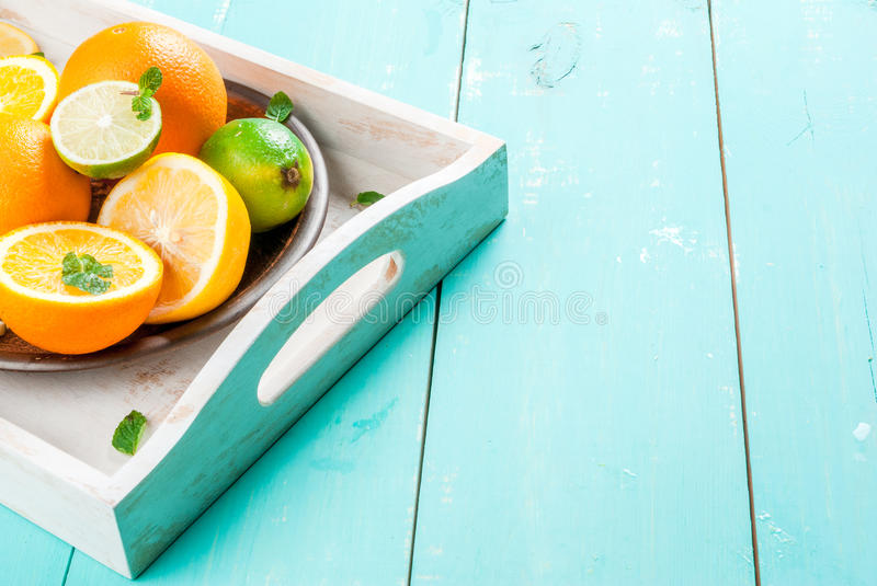 Tray with citrus fruits. Tray with whole and cut citrus orange, lemon, lime, decorated with mint leaves. On a blue wooden table, copy space stock photos
