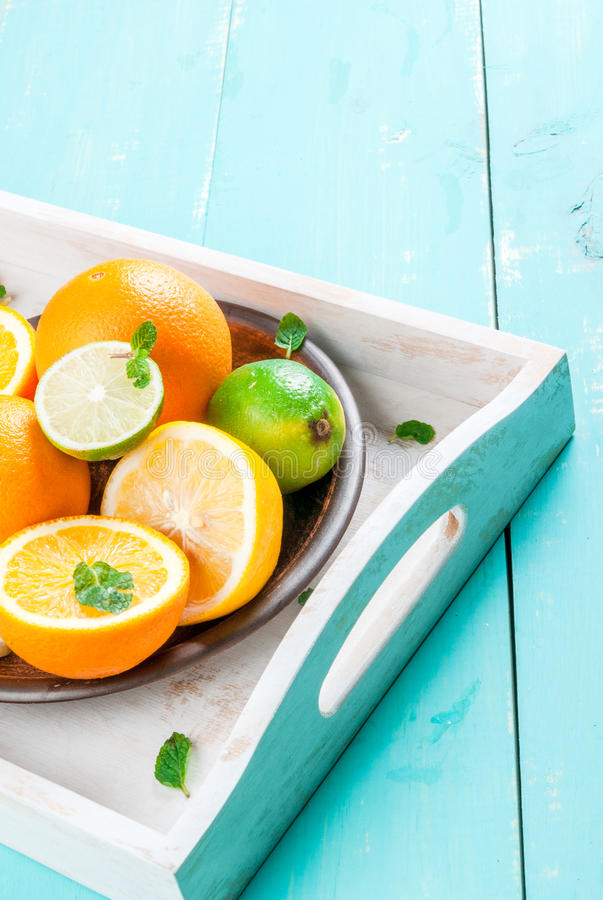 Tray with citrus fruits. Tray with whole and cut citrus orange, lemon, lime, decorated with mint leaves. On a blue wooden table, copy space stock images