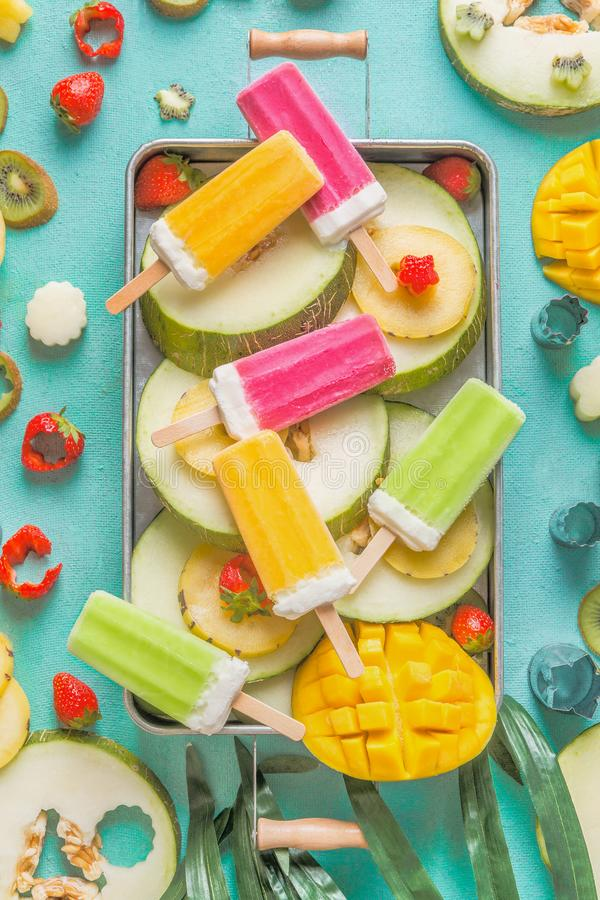Tray with colorful Ice cream popsicles with fresh sliced fruits and berries ingredients on light blue background, top view royalty free stock photography