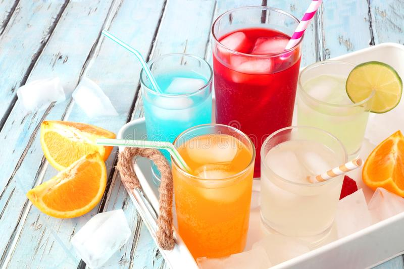 Tray of cool summer drinks against rustic blue wood. Tray of cool colorful summer drinks against a rustic wood background stock photography