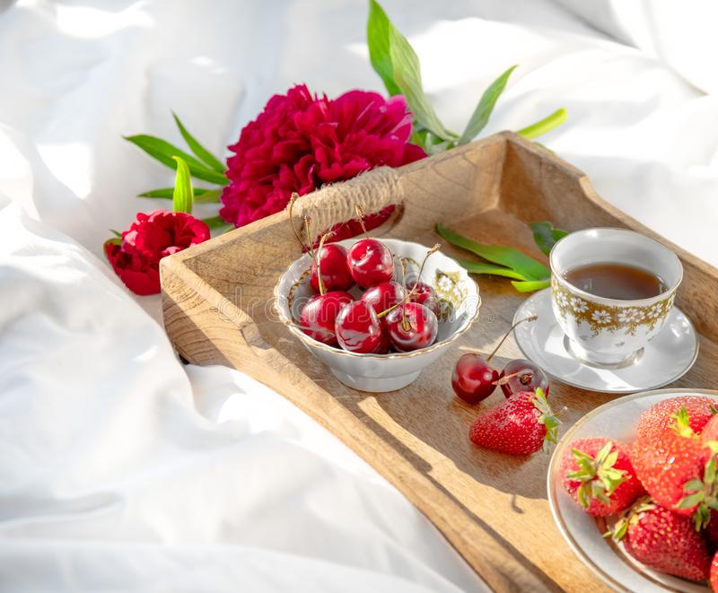 Tray with delicious breakfast on bed. Peony and wooden rustic tray with bowls of strawberries and sweet cherry and cup of coffe on a white bedlinen. Morning mix royalty free stock photo