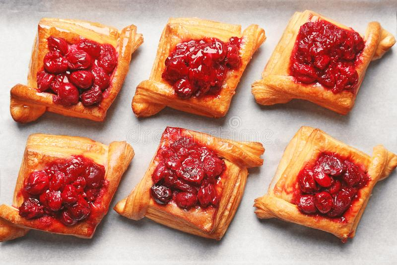 Tray with delicious puff pastries and cherry royalty free stock photography