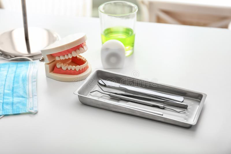 Tray with dentist\'s tools, mask and artificial jaw on light table in doctor\'s office royalty free stock photo