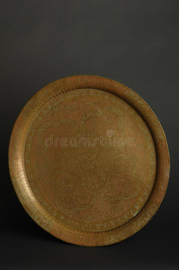 Tray with engraving. Ancient oriental metal tray on dark background. antique bronze tableware royalty free stock images