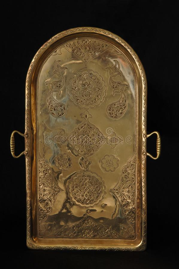 Tray with engraving. Ancient oriental metal tray on dark background. antique bronze tableware stock image