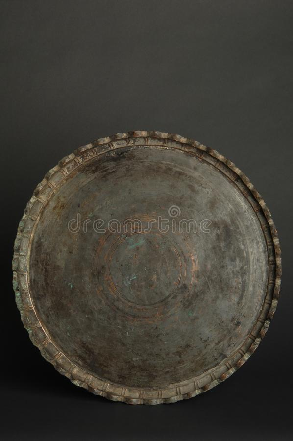 Tray with engraving. Ancient oriental metal tray on dark background. antique bronze tableware stock photos