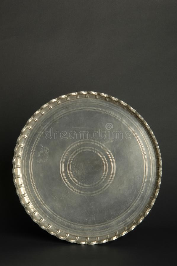 Tray with engraving. Ancient oriental metal tray on dark background. antique bronze tableware royalty free stock photography