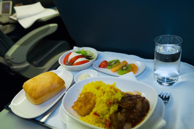 Tray of food on the airplane. Food served on board of business class airplane on the table. Tray of food in the airplane. Tray of food on the plane, business stock photography