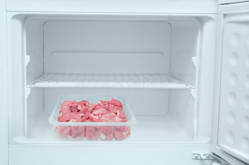 Tray with fresh chopped meat inside white freezer.Close-up royalty free stock images
