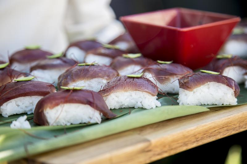 A tray full of sushi carried by a waiter. In a wood trail stock photo